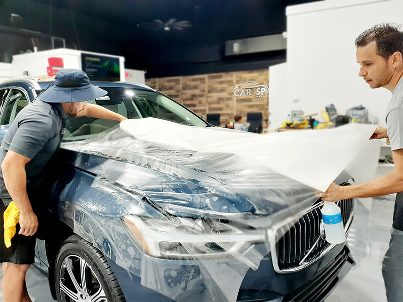 Detailers installing pain protection film in a SUV